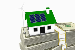 Green energy conceptual rendering of a house with a wind turbine and solar panels on a stack of hundred dollar bills.
