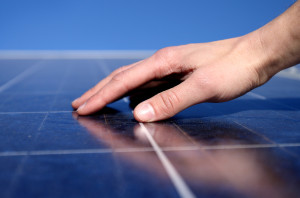 A hand is seen feeling the solar panel